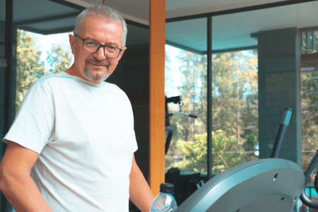 Mature man in the gym with a bottle of water exercises