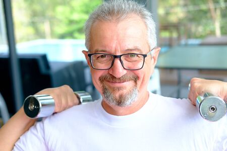A mature man with a beard and glasses holds dumbbells