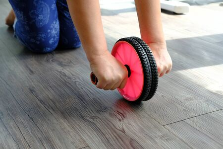 woman with gymnastic wheel roller does exercises for belly
