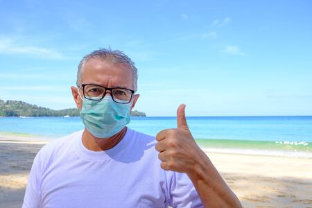 Mature man in white t-shirt and medical mask on his face Banco de Imagens