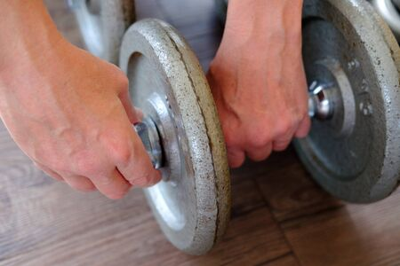 Hands fasten extra weight to a dumbbell for gym