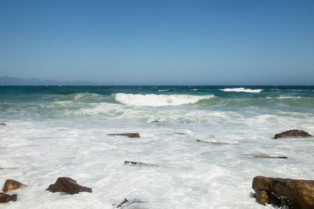 Foam and waves of the Atlantic Ocean with stones of the coast. Background photo Banco de Imagens
