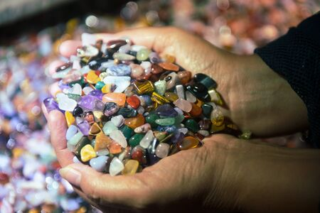 Many kinds of gems in womans hands