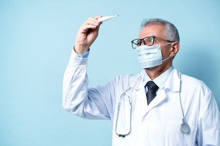 Senior doctor in glasses and a mask checks the temperature of the patient Banco de Imagens