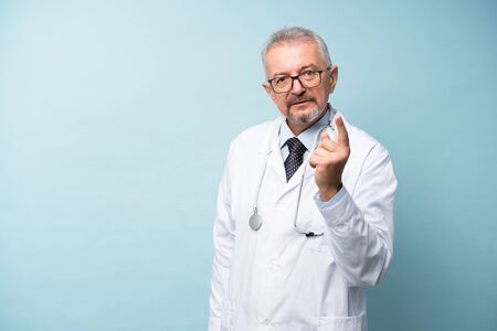 Senior doctor with a beard and glasses points a finger at the beholder Banco de Imagens