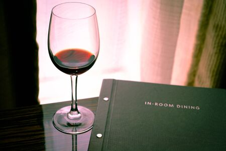 A glass of wine and a dinner menu on the background of a window and curtains Banco de Imagens - 148615512