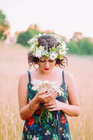Girl with flower crown posing in the field during sunset Archivio Fotografico