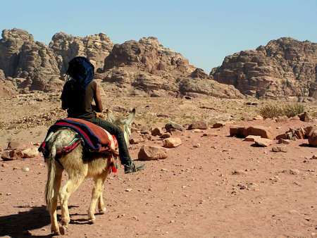 A bedouin riding his mule photo