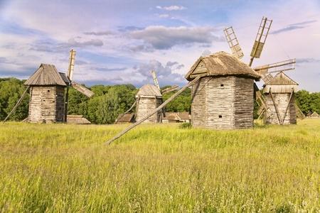 crop margin: Group of windmills standing on the meadow in museum of folk arts in Kiev, Ukraine