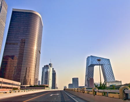 move forward: Modern buildings in Beijing at sunrise seen from the road