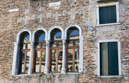 Fragment of the ancient palazzo wall with traditional Venetian arched windows reflecting roof of the opposite building on Grand Canal in Venice, Italy