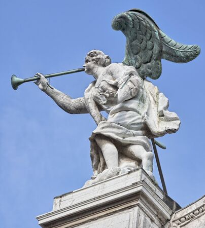 Statue of marble angel with bronze wings and trumpet on the roof of church Santa Maria di Giglio in Venice, Italy