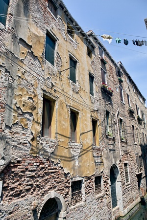 Rear shabby side with dilapidated plaster of a building on a Venetian canal in Venice, Italy