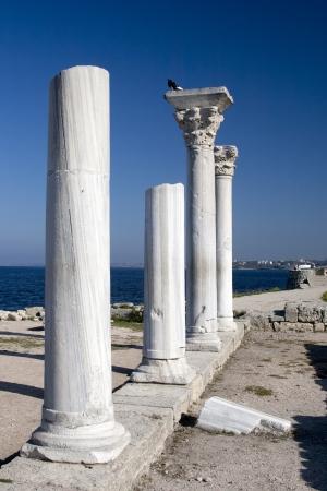Marble columns of Ancient Greek basilica on background of the see in Chersonesus Taurica near Sevastopol in Crimea, Ukraine