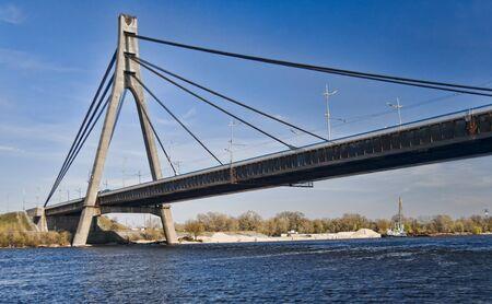 Suspension bridge across the blue Dnieper river in spring in Kiev, Ukraine