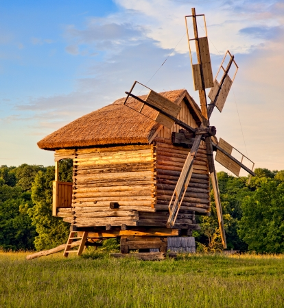crop margin: Antiguo molino de viento de madera en el bosque al atardecer en Folk Arts Museum Pirogovo, Kiev, Ucrania Foto de archivo
