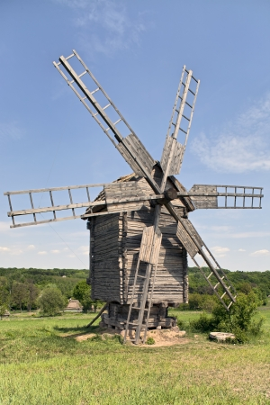 Old wooden windmill on the grassland on sunny day at Folk Arts museum Pirogovo in Kiev, Ukraine photo