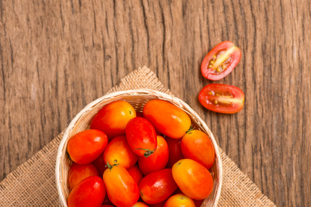 gunny: tomato on gunny and wooden background(focus tomato in basket)