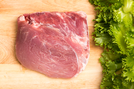 salad greens: salad greens and uncooked pork on chopping block Stock Photo
