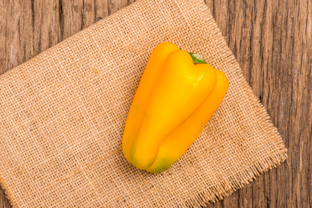 gunny: yellow sweet pepper and gunny on wooden background Stock Photo