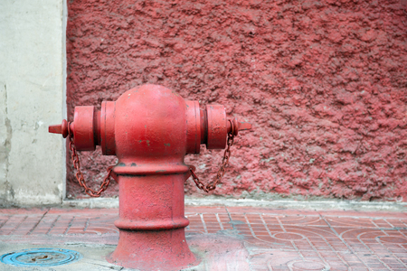 standing alone: Red fire hydrant standing alone on footpath Stock Photo