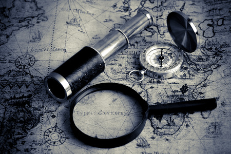 azimuth: Old vintage compass ,telescope and magnifying glass on vintage map (Black and White tone)