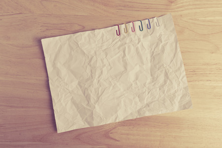 nota de papel: Clip de papel en el papel arrugado en el fondo de madera
