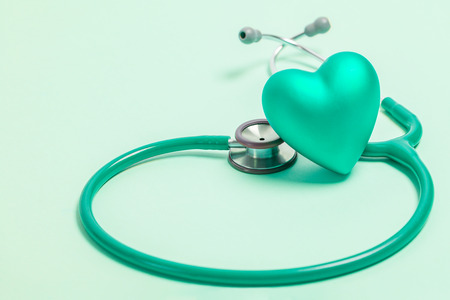 Stethoscope and green heart on green background