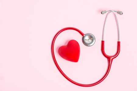 Stethoscope and red heart on pink background Stock Photo