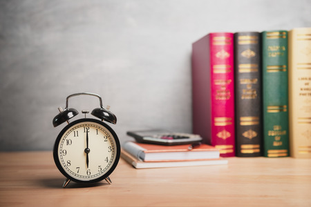 Six oclock, Closeup retro alarm clock on table with blurred office equipment background Stock Photo