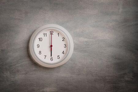 Clock showing six o clock on gray wall