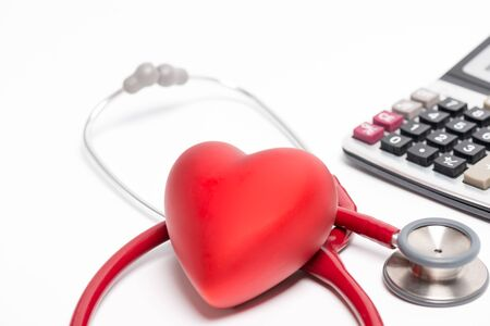 Stethoscope and red heart with calculator isolated on white background