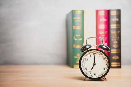 seven o'clock: Clock showing seven o�clock on table with blurred background Stock Photo