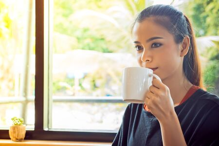 Woman drinking coffee at coffee cafe Stock Photo