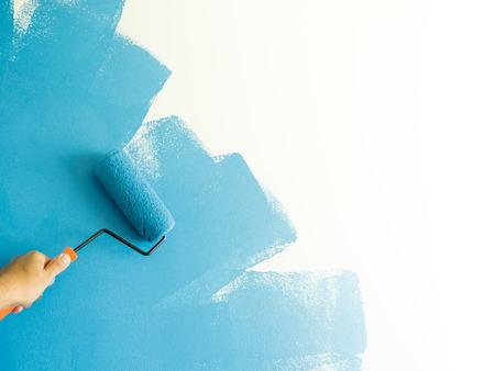青色で塗装ローラーを持つ手