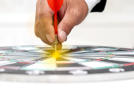 Businessman put the red dart arrow on center of dart board. Goal setting concept business strategy. Foto de archivo - 122022751