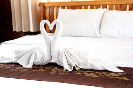 Towels folded in couple of swan shape with heads in heart shape on bed at the resort Foto de archivo - 122022758