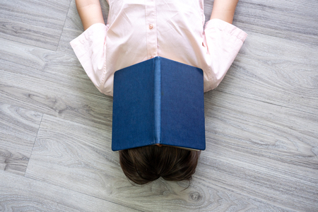 Little boy hide face with open book laying in floor. Child sleep with story book on face Foto de archivo - 122022764