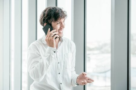 Young man wearing casual clothes talking on a mobile phone Foto de archivo - 131993236
