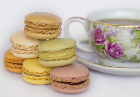 tea and biscuits: Stack of the traditional delicious french cookies isolated on white with the flowered tea cup on the background.