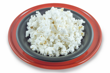 Popcorn on red and black plates on white isolated.