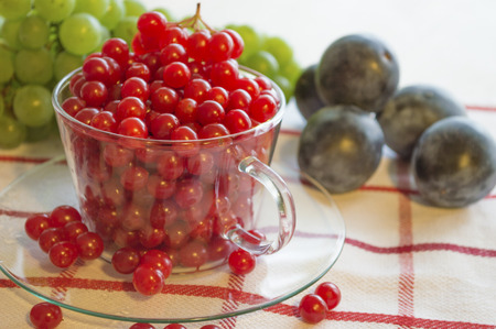 Green grapes and red viburnum in clear glass on the white cloth with red stripes. Banco de Imagens