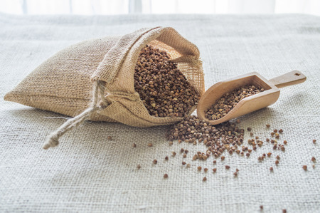 Bag of the buckwheat with the wooden scoop on sackcloth Stock Photo