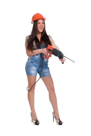 Young woman in orange helmet holding hammer drill photo
