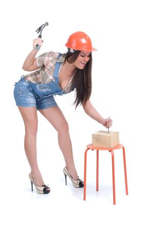 Emotional young woman in orange helmet hammer in nail Stock Photo - 5639667
