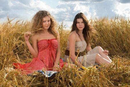 Two beautiful slavonic girls on picnic in wheat field photo
