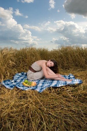 Beautiful slavonic girl on picnic in wheat field photo