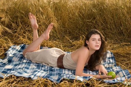 slavonic: Beautiful slavonic girl on picnic in wheat field with apple