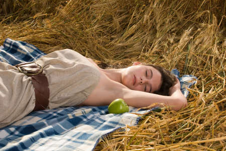 cute young farm girl: Beautiful slavonic girl on picnic in wheat field with apple
