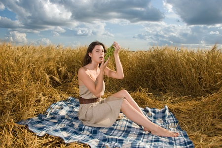 slavonic: Beautiful slavonic girl on picnic in wheat field with grapes